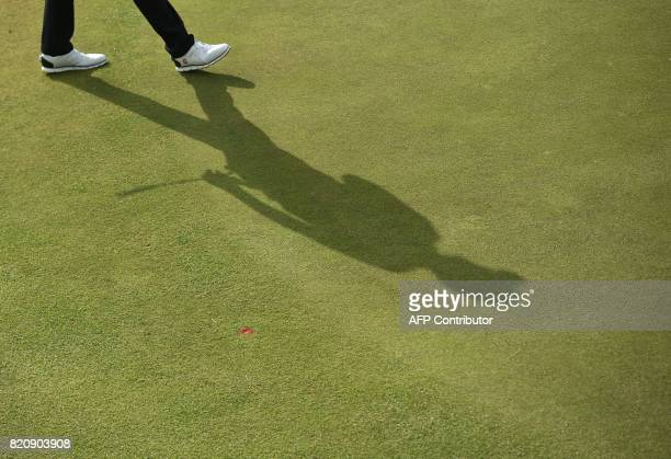 TOPSHOT The shadow of England's Ian Poulter on the 12th green during his third round on day three of the Open Golf Championship at Royal Birkdale...