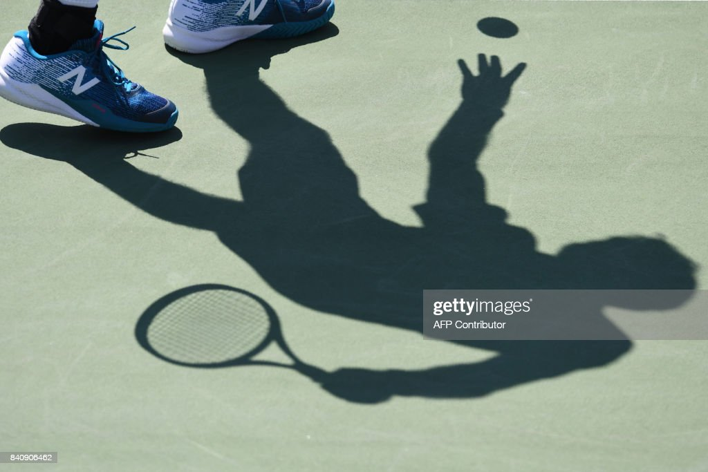 the shadow of France's Jeremy Chardy is seen against France's Gael Monfils during their Qualifying Men's Singles match at the 2017 US Open Tennis Tournament on August 29, 2017 in New York. / AFP PHOTO / Timothy A. CLARY