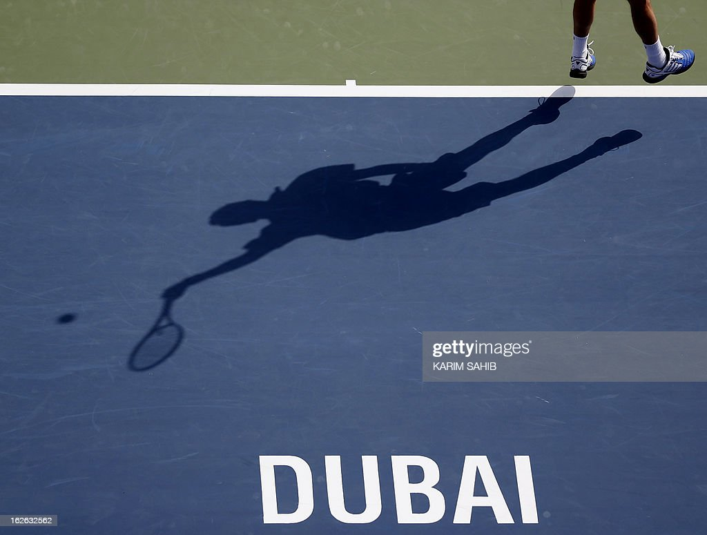 The shadow of France's Paul-Henri Mathieu is cast on the ground as he serves to Italy's Andreas Seppi during their ATP Dubai Open tennis match in the Gulf emirate on February 25, 2013. AFP PHOTO/KARIM SAHIB