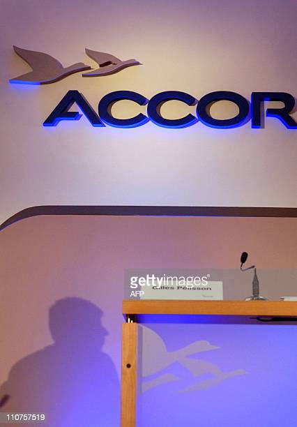 The shadow of French hotel group Accor Chief Executive Officer Gilles Pelisson is pictured on the wall with the new Accor's visuel identity during a...