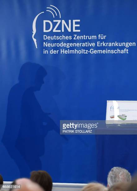 The shadow of German Chancellor Angela Merkel is seen as she arrives on stage prior a speech during her visit at the Research Center for...