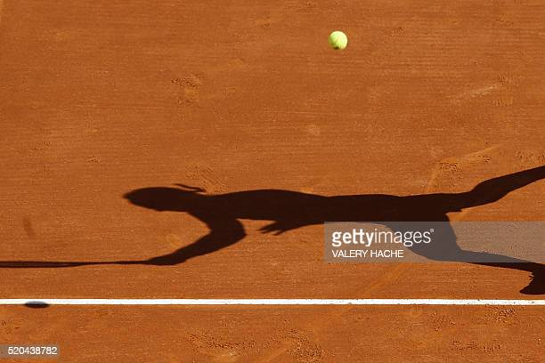 The shadow of Italy's Marco Cecchinato is pictured as he returns the ball to Canada's Milos Raonic during the MonteCarlo ATP Masters Series...