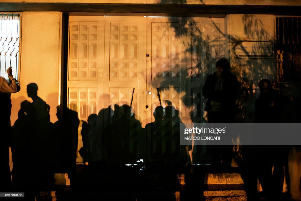 The shadow of Palestinians is cast on the door of the al-Shifa hospital morgue in Gaza City on November 20, 2012. Two cameramen from Hamas-owned Al-Aqsa TV were among six people killed in Israeli air raids on the Gaza Strip, raising Tuesday's death toll to 20, a Hamas spokesman said. AFP PHOTO/MARCO LONGARI