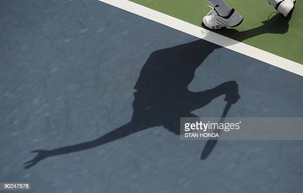 The shadow of PaulHenri Mathieu of France is cast on the court as he serves to Mikhail Youzhny of Russia during their first round US Open match at...