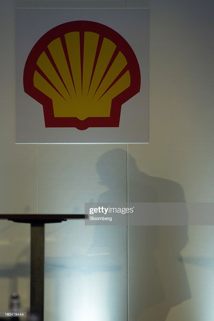 The shadow of Peter Voser, chief executive officer of Royal Dutch Shell Plc, is seen on a wall beneath a logo as he speaks during a news conference to announce the company's fourth-quarter results in London, U.K., on Thursday, Jan. 31, 2012. Royal Dutch Shell Plc, Europe's biggest energy company, said investment will increase after fourth-quarter profit missed analyst estimates on weaker North American fuel prices. Photographer: Simon Dawson/Bloomberg via Getty Images