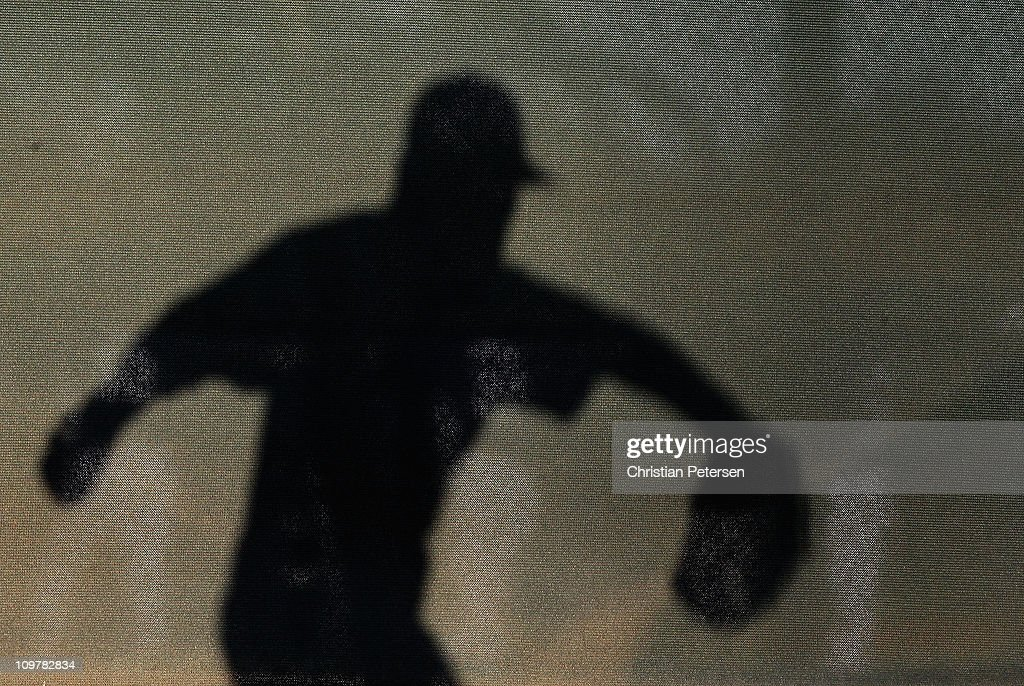 The shadow of pitcher Scott Elbert #57 of the Los Angeles Dodgers as he throws warm ups before the spring training game against the San Francisco Giants at Camelback Ranch on March 4, 2011 in Glendale, Arizona.