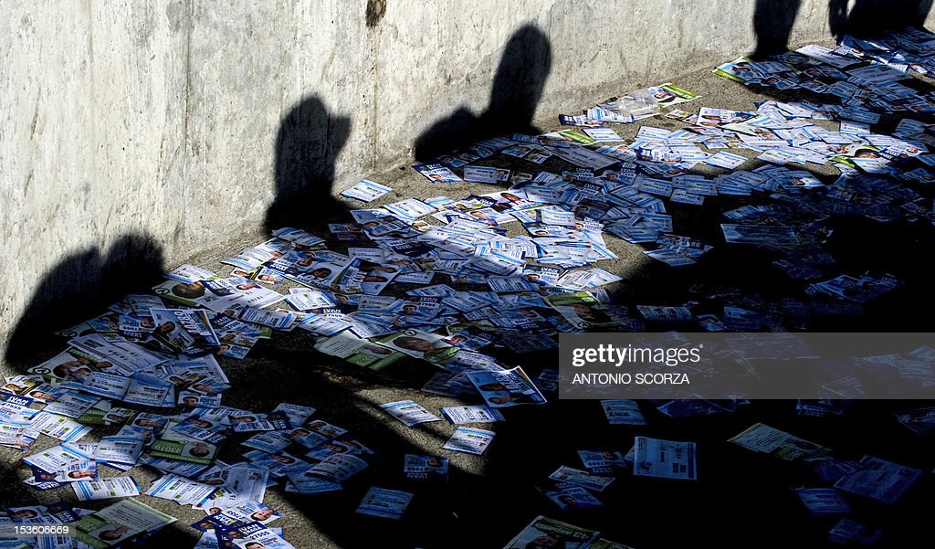 The shadow of voters is refectected over pamphlets as they queue a polling station at a school in Rio de Janeiro's Rocinha shantytown, Brazil, on October 7, 2012 during the nationwide municipal elections. Nearly 139 million Brazilians are registered to elect 5,561 mayors and 48,000 municipal councilors among 450,000 candidates representing more than 20 political parties. AFP PHOTO/ANTONIO SCORZA