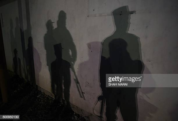 TOPSHOT The shadows of Afghan police officers are seen near the site of an attack on the Spanish embassy compound in Kabul on December 11 2015...