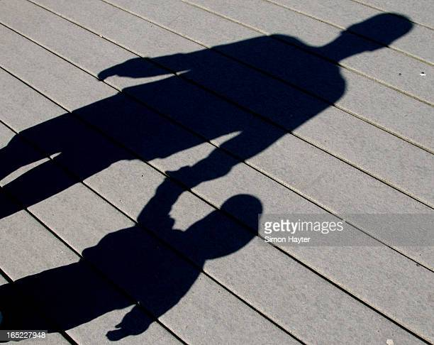 PEDOPHILIA 06/20/04 The shadows of Chris Matson and his son Sam are cast along the boardwalk at Sir Casimir Gzowski Park as they walk in the sun on a...