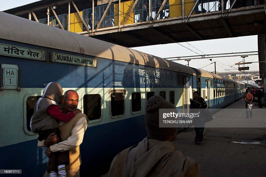 The shadows of disembarking Indian passengers are cast on a train coach as other passengers walk on the platform at the Hazrat Nizamuddin railway station in New Delhi on February 26, 2013, when the railway budget is due to be tabled in Parliament. The railway, the country's largest employer with some 1.4 million people on its payroll, runs 11,000 passenger and freight trains and carries 19 million people daily.