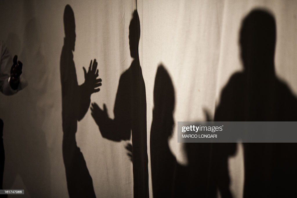 The shadows of members of a dance group of Sudanese refugees from the Darfur region are seen on sheets as they perform on stage at a cultural centre in south Tel Aviv on February 15, 2013. Hundreds of Sudanese refugees take part in the cultural festival to share with local Israeli audience samples of their cultural heritage. AFP PHOTO/MARCO LONGARI