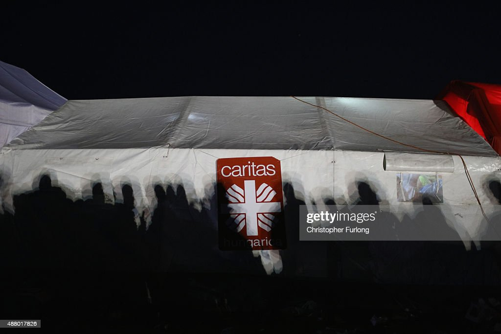 The shadows of migrants fall on the tent of the Catholic aid organistaion Caritas at the Hungarian border with Serbia on September 12 2015 in Roszke...