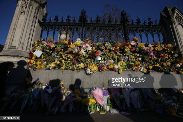 The shadows of onlookers are cast on floral tributes to the victims of the March 22 terror attack pushed through the railings of the Houses of...