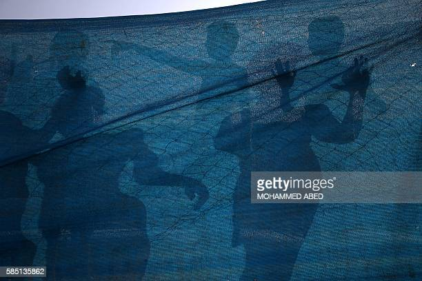 TOPSHOT The shadows of Palestinians are seen on a piece of gauze as they cool down at a pool in Gaza City on August 2 2016 / AFP / MOHAMMED ABED
