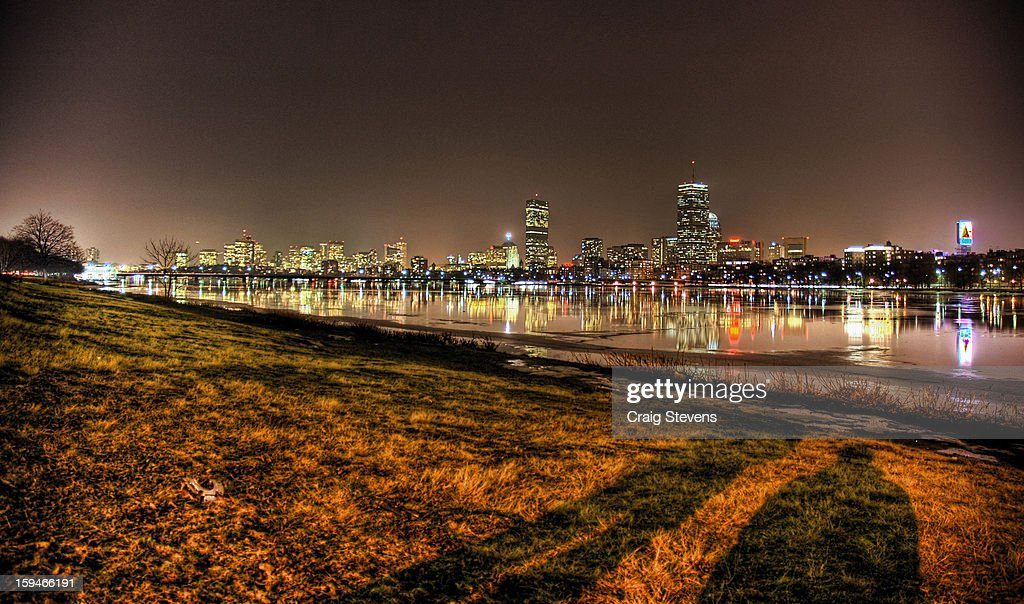 CONTENT] The shadows of two photographers are cast against the grass next to the Charles River in Boston, Massachusetts on a cold evening in February