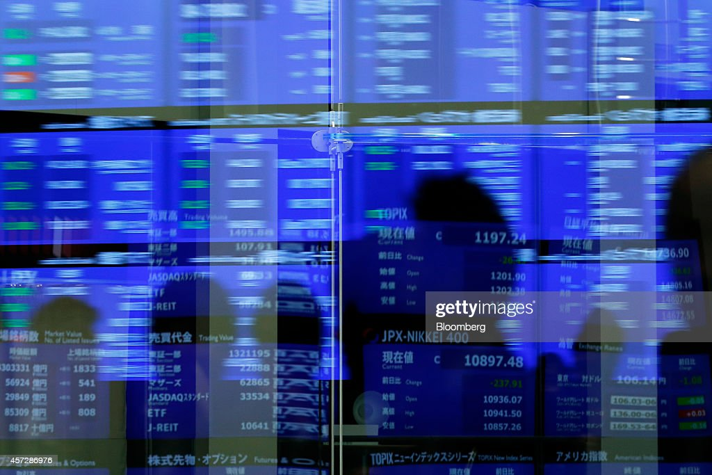 The shadows of visitors and various stock figures are reflected on glass panels at the Tokyo Stock Exchange operated by Japan Exchange Group Inc in...