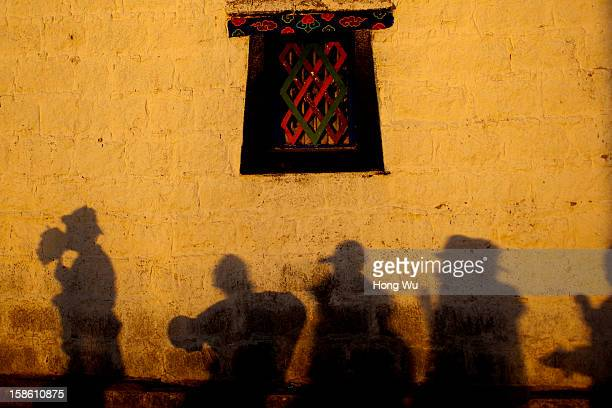 The shadows show Tibetan Buddhism believers pray outside the Jokhang Monastery August 15 2012 in Lhasa China Lhasa is the administrative capital of...