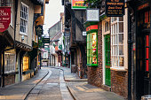 Early morning on the famous narrow medieval street in the historic centre of York, filled with shops, pubs and cafes.