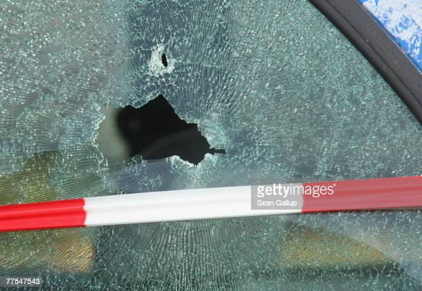 The shattered window of a car struck by a bullet is visible outside a branch of Postbank bank after an attempted robbery that left one guard dead...