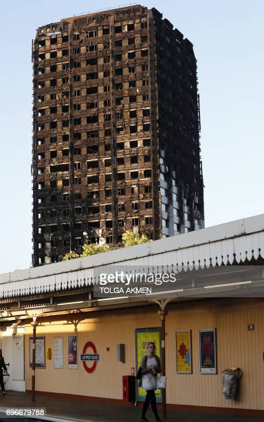 The shell of Grenfell Tower looms over Latimer Road underground station in west London on June 16 two days after a the fire gutted the residential...