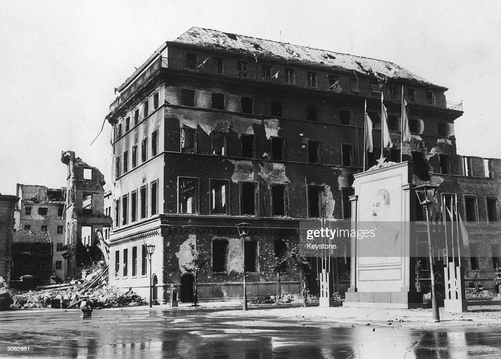 The shell of the Adlon Hotel in the Unter den Linden Berlin still standing but windowless Beside it is a large picture of Stalin