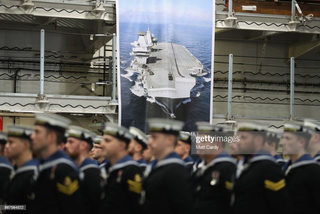 The ship's company arrives in the hanger ahead of the Commissioning Ceremony of HMS Queen Elizabeth at HM Naval Base on December 7, 2017 in Portsmouth, England.