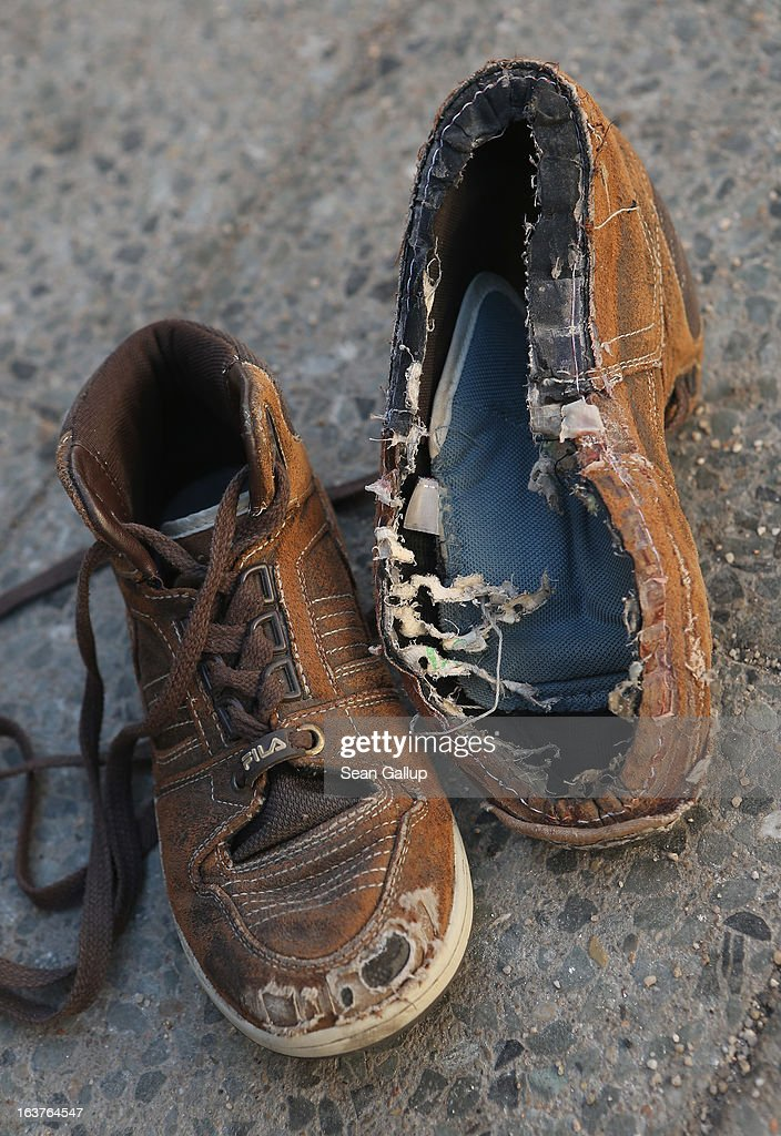 The shoes, including one missing a sole, of an eight-year-old boy who, together with his brother, was found recently on a wintry evening in a city underground train by police, lie placed by the photographer on the sidewalk outside the Bahnhofsmission homeless kitchen where the boys were brought on March 15, 2013 in Berlin, Germany. Passengers alerted police to the boys, aged four and eight and who were poorly clad in the sub-zero temperatures, and police brought them to the Bahnhofsmission, where the boys received food and the eldest a replacement pair of shoes. Police eventually succeeded in contacting the mother, who is a low-income single mother whose husband is in jail. Poverty and especially child poverty have been a recurring theme as the number of people in Germany below the official poverty line has increased in recent years. One Berlin tabloid ran a story about the shoes on its front page March 13.