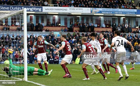 The shot by Jack Cork of Swansea City is deflected by Kieran Trippier of Burnley past goalkeeper Thomas Heaton of Burnley for an own goal during the...