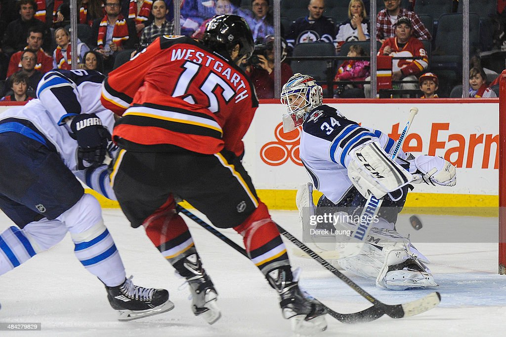 The shot of Kevin Westgarth #15 of the Calgary Flames goes wide of Michael Hutchinson #34 of the Winnipeg Jets during an NHL game at Scotiabank Saddledome on April 11, 2014 in Calgary, Alberta, Canada. The Jets defeated the Flames 5-3.