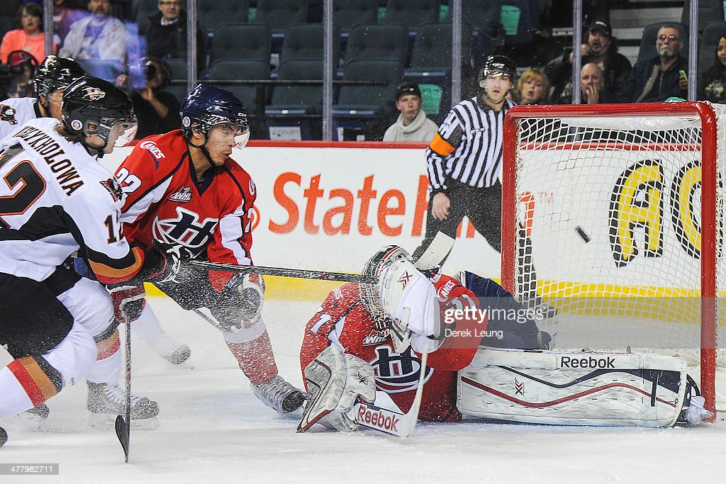 The shot of Landon Welykholowa #12 of the Calgary Hitmen is deflected wide of the net by Stuart Skinner #31 of the Lethbridge Hurricanes during a WHL game at Scotiabank Saddledome on March 11, 2014 in Calgary, Alberta, Canada.