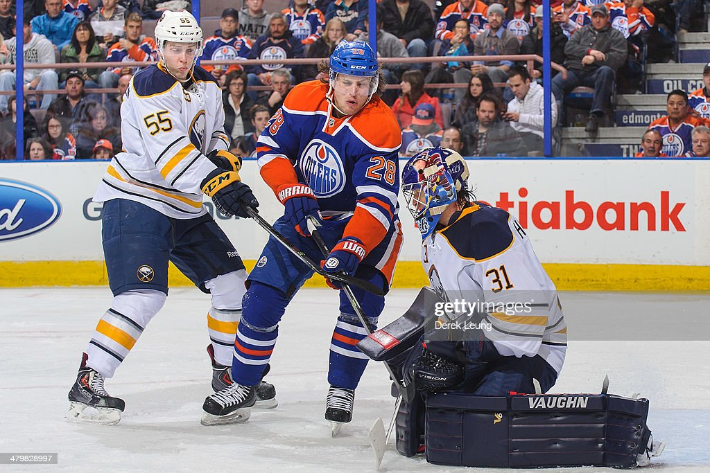 The shot of Ryan Jones #28 of the Edmonton Oilers is stopped by <a gi-track='captionPersonalityLinkClicked' href=/galleries/search?phrase=Matt+Hackett&family=editorial&specificpeople=4161891 ng-click='$event.stopPropagation()'>Matt Hackett</a> #31 of the Buffalo Sabres during an NHL game at Rexall Place on March 20, 2014 in Edmonton, Alberta, Canada.