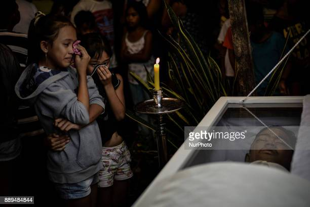 The siblings of 15yearold Mark Lorenz Salonga who was killed by unidentified assailants weep during his funeral wake in Taguig Metro Manila...