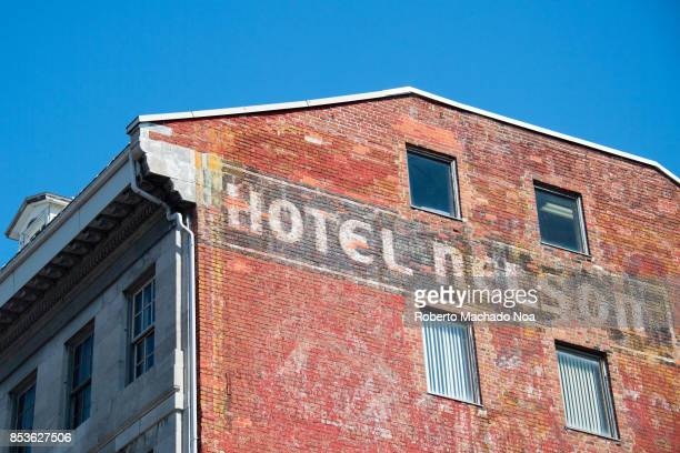 The side wall of Hotel Nelson building on the JacquesCartier Square Old Montreal The old red brick wall has four glass windows The area is Unesco...