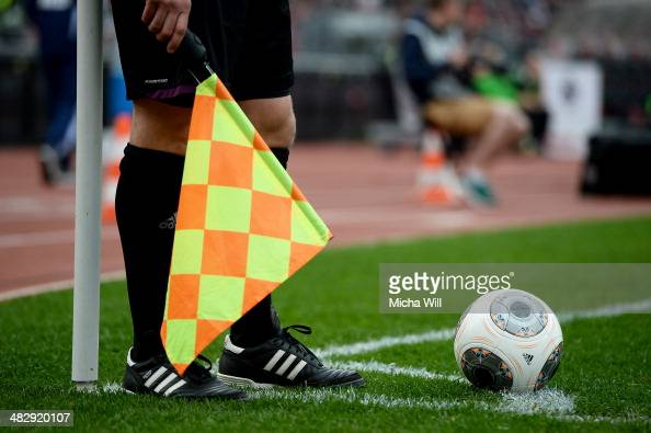The sideline referee stands next to the corner flag waiting for a player to kick the ball during the Bundesliga match between 1 FC Nuernberg and...