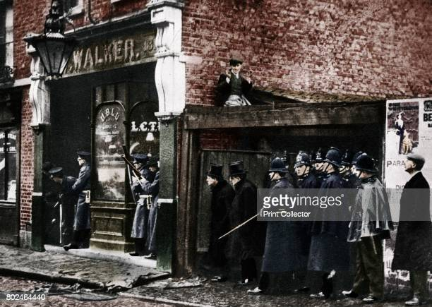 The Sidney Street siege Whitechapel London Winston Churchill then Home Secretary the left of the tophatted figures is earnestly watching the...