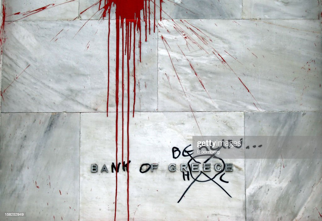 The sign at the central bank of Greece is seen covered in graffiti, the sign now reads 'Bank of Berlin', following demonstrations in Athens, Greece, on Sunday, Feb. 12, 2012. Greek Prime Minister Lucas Papademos won parliamentary approval for austerity measures to secure an international bailout after rioters protesting the measures battled police and set fire to buildings in downtown Athens. Photographer: Simon Dawson/Bloomberg via Getty Images