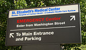 The sign for St Elizabeth's Medical Center a member hospital of Caritas Christi and a Catholic Health Care System points to the Emergency Center main...