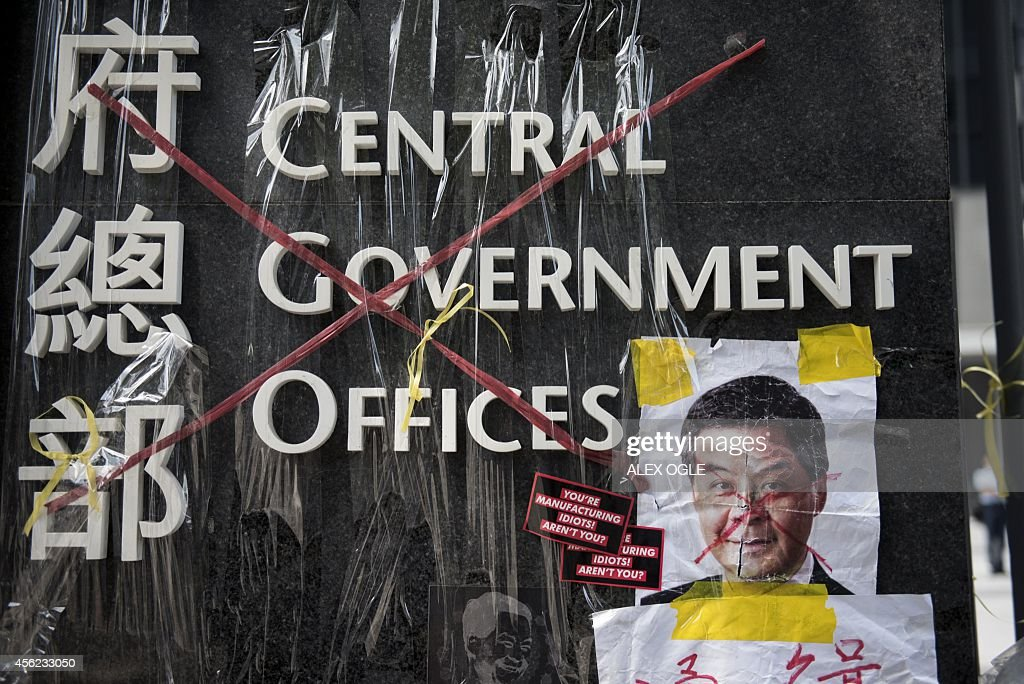 The sign for the Hong Kong central government offices is seen crossed out with red tape by democracy activists next to a defaced image of Hong Kong's...