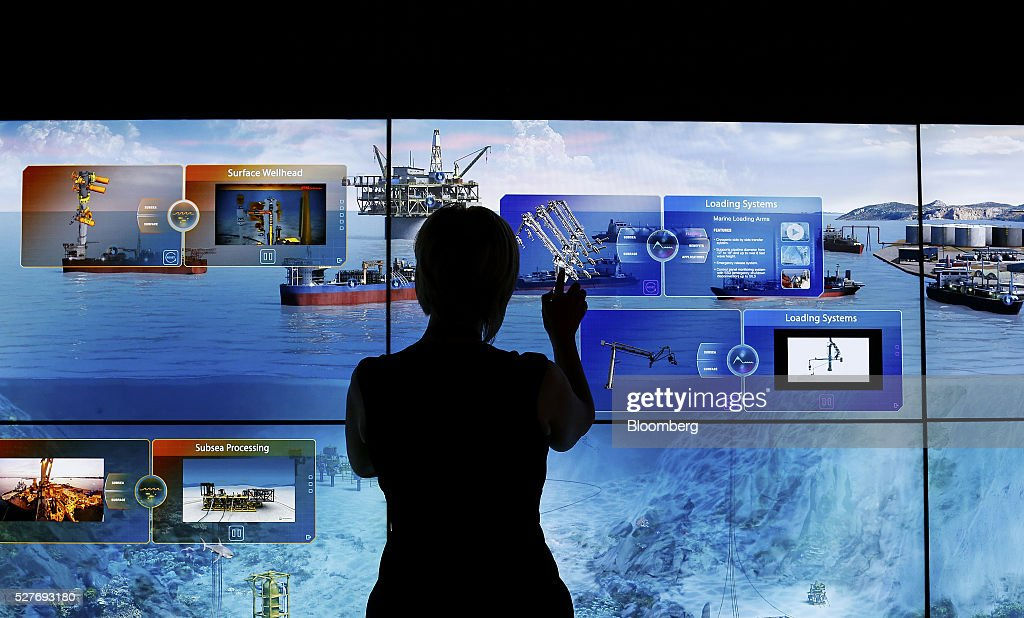 The silhouette is seen of a FMC Technologies Inc. employee is seen checking the interactive mural at the company's booth during the 2016 Offshore Technology Conference (OTC) in Houston, Texas, U.S., on Tuesday, May 3, 2016. The OTCgathers energy professionals to exchange ideas and opinions to advance scientific and technical knowledge for offshore resources. Photographer: Aaron M. Sprecher/Bloomberg via Getty Images