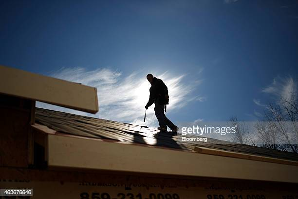 The silhouette of a construction worker is seen as he walks on a roof after nailing down roofing paper on top of an apartment building built by...