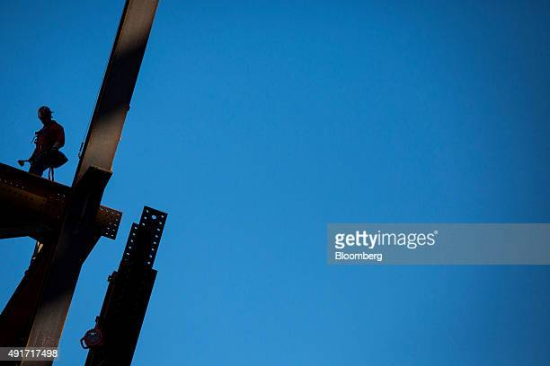 The silhouette of a contractor is seen working at 10 Hudson Yards before the start of a topping out ceremony in New York US on Wednesday Oct 7 2015...