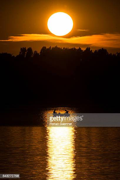 The silhouette of a couple in a boat is seen in the reflection of the setting sun on June 23 2016 in Bautzen Germany