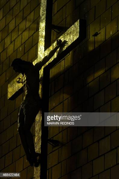 The silhouette of a crucified Christ at the main altar of the Church of the Rosary in San Salvador on March 6 2015 AFP PHOTO / Marvin RECINOS