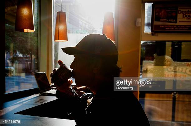 The silhouette of a customer drinking a cup of coffee is seen at a Tim Hortons Inc restaurant in downtown Vancouver British Columbia Canada on...