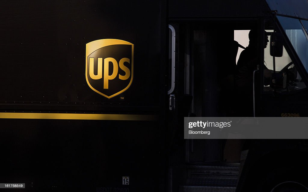 The silhouette of a driver is seen in a United Parcel Service (UPS) delivery truck at the distribution center in Sacramento, California, U.S., on Thursday, Feb. 14, 2013. 100 UPS delivery all-electric vehicles, developed by Electric Vehicles International (EVI), have been deployed this week and are said to eliminate the use of 126,000 gallons of fuel per year. Photographer: Ken James/Bloomberg via Getty Images