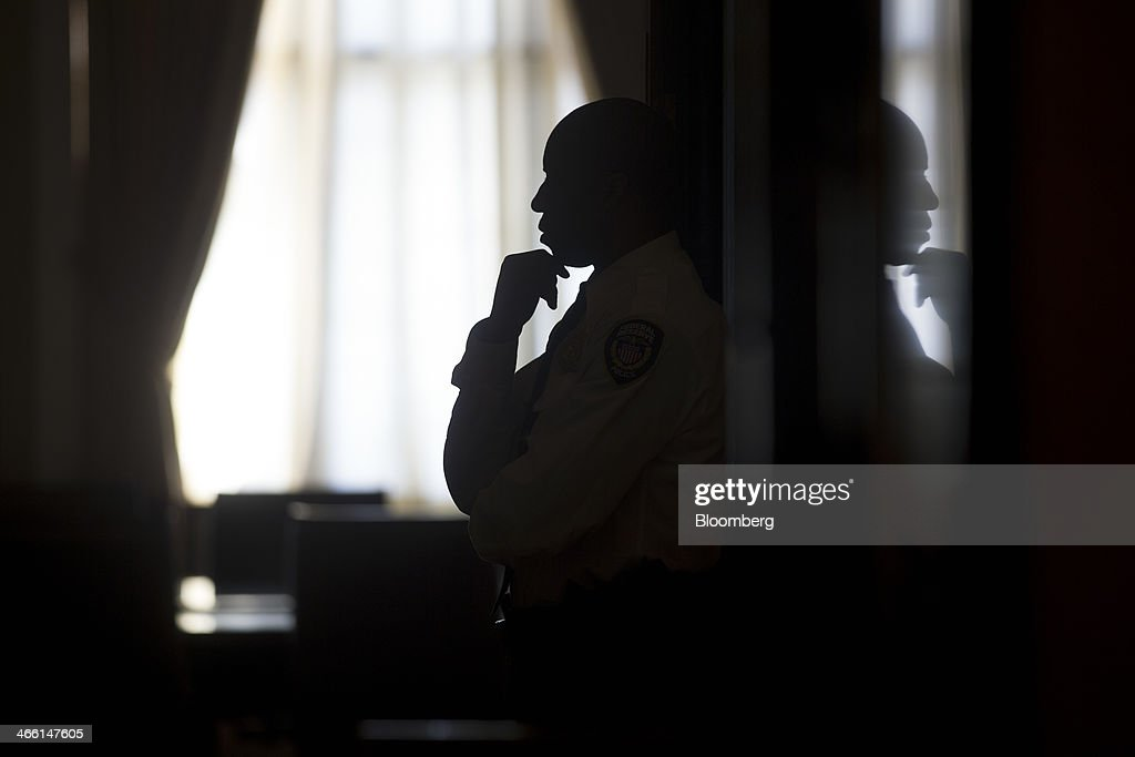 The silhouette of a Federal Reserve police officer is seen standing in an entryway before Ben S. Bernanke, chairman of the U.S. Federal Reserve, walks out of his office at the Federal Reserve in Washington, D.C., U.S., on Friday, Jan. 31, 2014. Janet Yellen takes over as Fed chairman beginning Feb. 1, succeeding Ben S. Bernanke, whose eight-year tenure ends today. Photographer: Andrew Harrer/Bloomberg via Getty Images