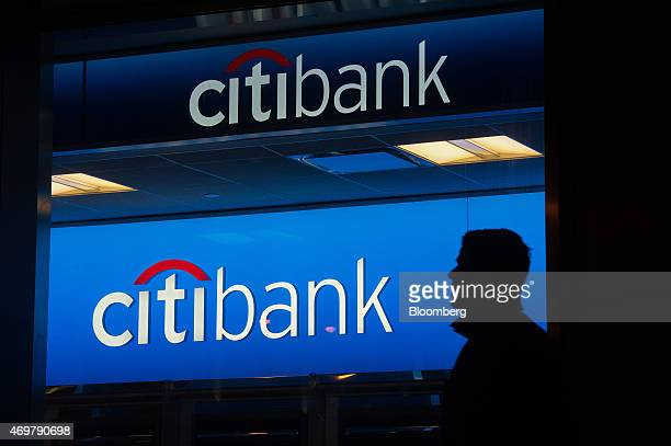 The silhouette of a pedestrian is seen walking past a Citigroup Inc Citibank branch at night in New York US on Saturday April 11 2015 Citigroup Inc...