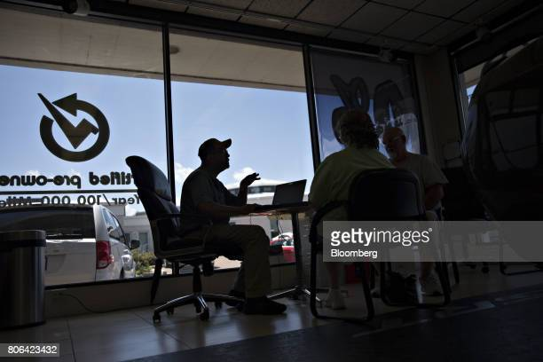 The silhouette of a salesman is seen as he works with a customer in the showroom of a Fiat Chrysler Automobiles car dealership in Moline Illinois US...