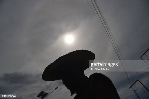 The silhouette of a soda vendor is seen during the solar eclipse that was partially visible in PortauPrince on August 21 2017 The solar eclipse in...