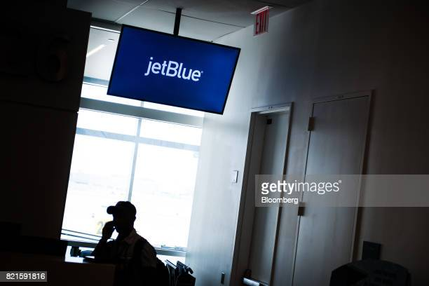 The silhouette of a traveler is seen underneath JetBlue Airways Corp signage at Terminal 5 inside John F Kennedy International Airport in New York US...